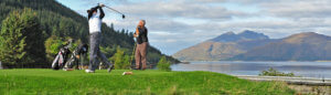 A photo of two men, one hitting a golf ball, on what appears to be mountainous islands.