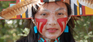 Native American girl in traditional garb with painted face.
