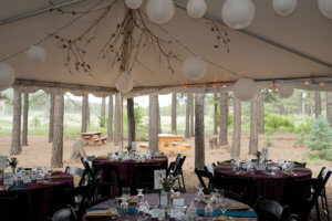 Outdoor tent with tables set with dinnerware.